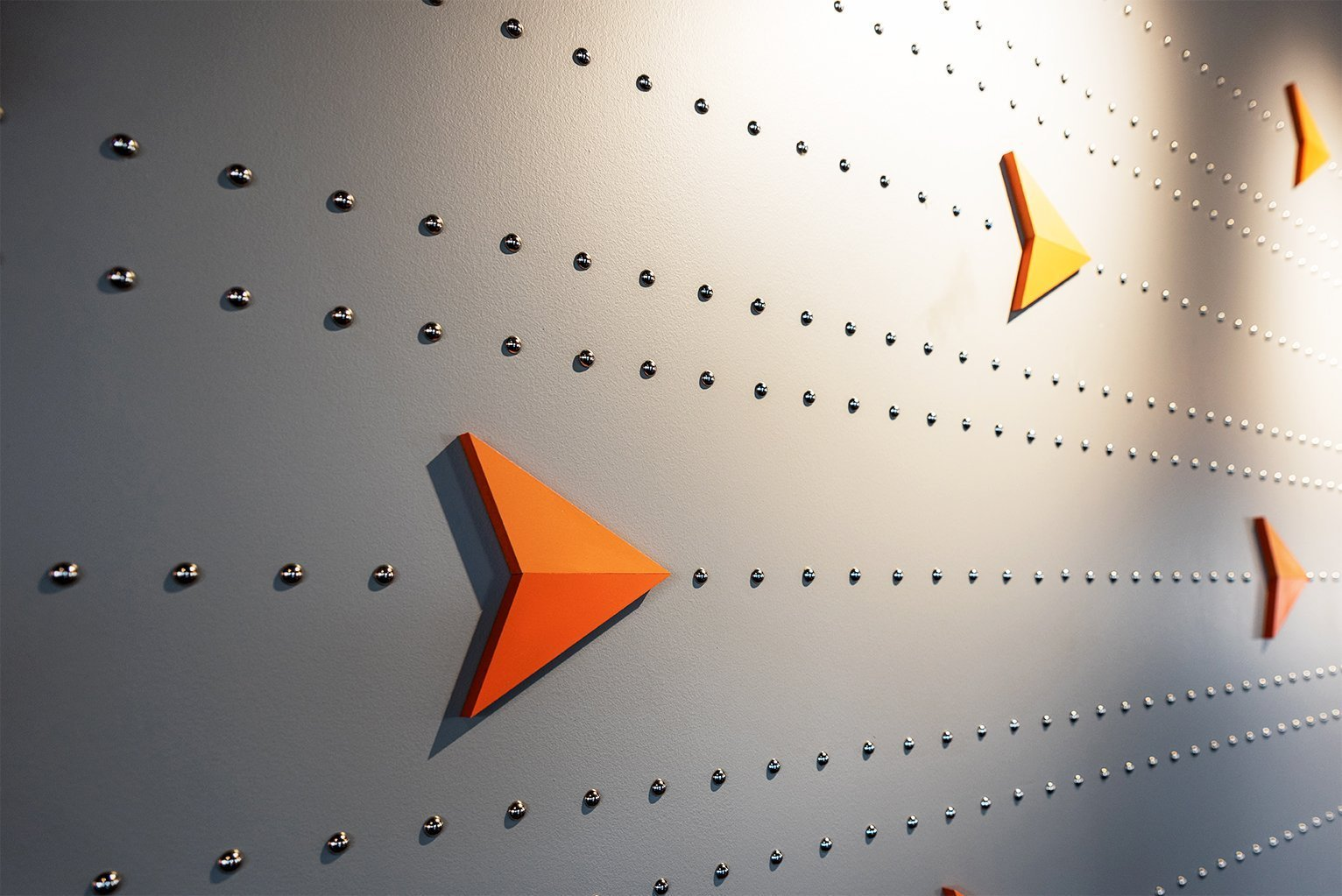 Close up of wall decoration showing the orange Up North arrow used in their logo in a linear pattern with lines of polished nail heads on a gray wall