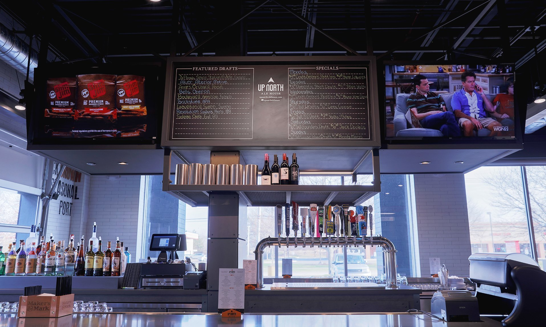 Close up of bar island featuring the chalkboard menu and two televisions along with the beer taps