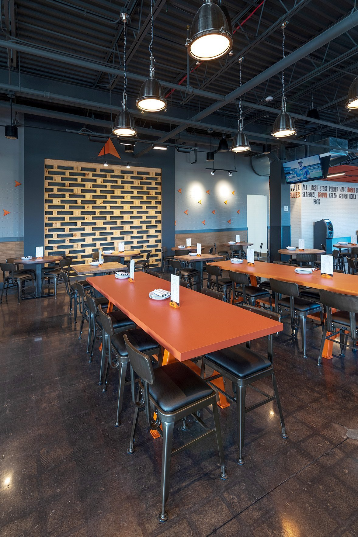 Orange community dining tables in front of the stage area with a custom stacked wood palette wall