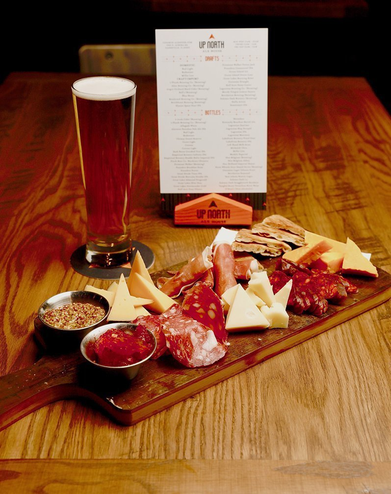 Table setting showing the Charcuterie board, freshly tapped beer, and table top menu