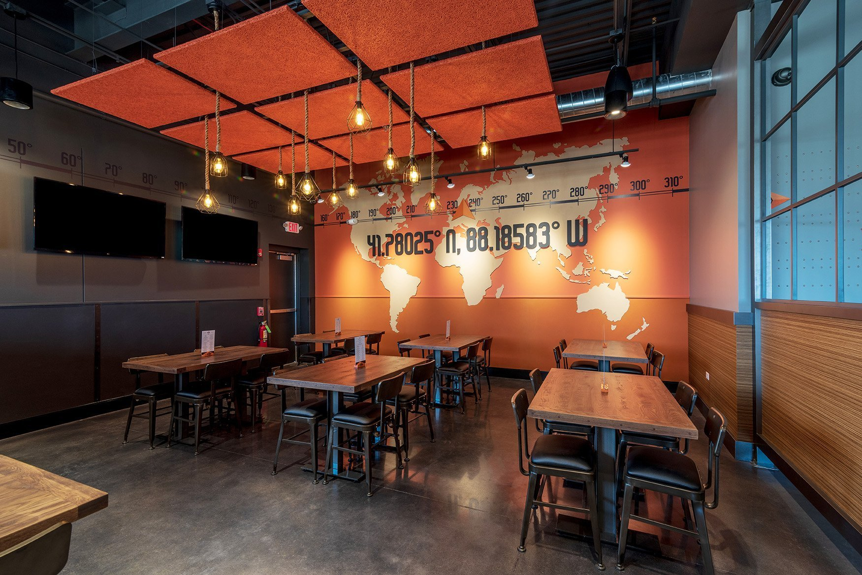 Inside Up North Ale House's semi private dining room featuring a bright orange wall with a large graphic the world map and the latitude and longitude numbers for the location of the restaurant