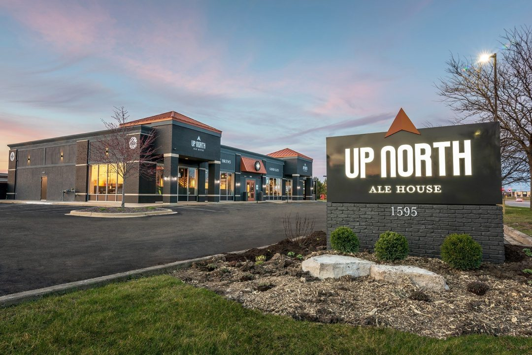 Building Exterior Showing Monument Sign with the Up North logo in front of the building. The building is a charcoal gray color with copper decorative roof elements.