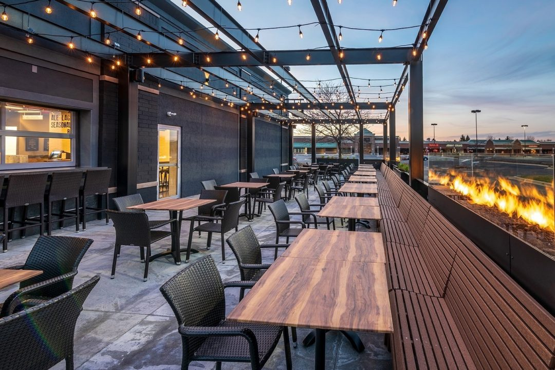 The patio at Up North Ale House features wood tables and bench seating along a firewall and under a canopy of strung Edison lights