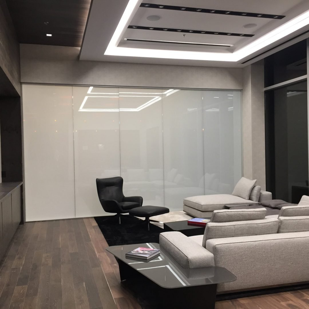 This luxurious CEO office space features leather lounge chairs in cream and black with dark wood flooring and dark side walls. The back wall is a frosted white glass that overlooks the showroom on the floor below and the ceiling features an illuminated cove soffit
